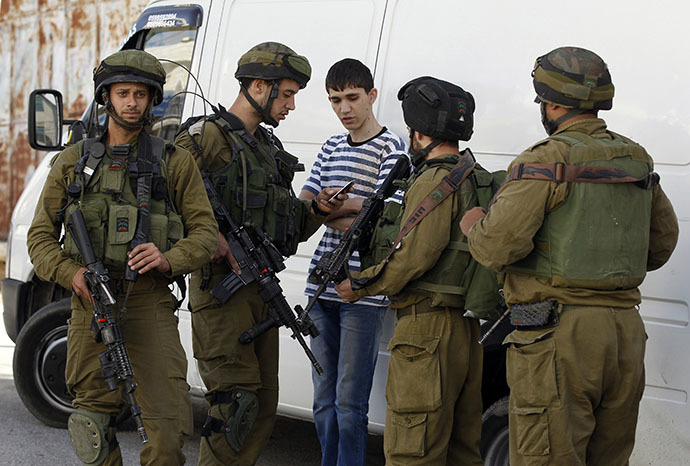 Israeli soldiers search a Palestinian youth during an operation to locate three Israeli teens in the West Bank city of Hebron June 16, 2014. (Reuters / Ammar Awad)