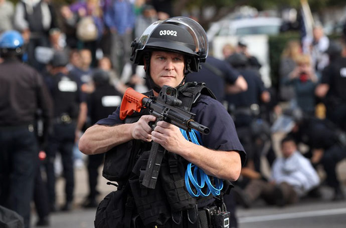 """A policeman in riot gear points his weapon at demonstrators as police arrest a protester at the """"Occupy Denver"""" camp on October 29, 2011 in Denver, Colorado. (AFP Photo / Getty Images / John Moore)"""