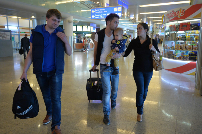 Zvezda TV channel correspondent Evgeny Davydov, center, with his family and sound engineer Nikita Konashenkov on their arrival at Moscow's Sheremetyevo airport. (RIA Novosti/Alexey Kudenko)