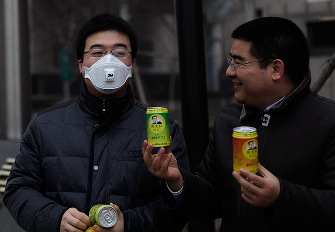 ARCHIVE PHOTO: Chinese multimillionaire Chen Guangbiao (R) gives a can of fresh air to a man wearing a mask on a hazy day in central Beijing, January 30, 2013 (Reuters / Barry Huang)