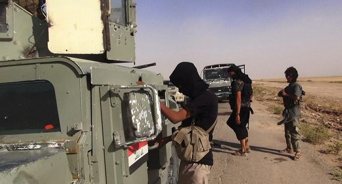 An image made available by the jihadist Twitter account Al-Baraka news on June 13, 2014 allegedly shows Islamic State of Iraq and the Levant (ISIL) militants inspecting abandoned Iraqi army vehicles at an undisclosed location close to the Iraqi-Syrian border, in the district of Sinjar, northwest Iraq. (AFP Photo)