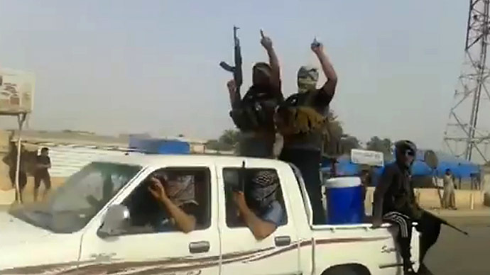 An image grab taken from a video uploaded on Youtube on June 17, 2014, allegedly shows militants from the Islamic State of Iraq and the Levant (ISIL) parading with their weapons in the northern city of Baiji in the in Salaheddin province. (AFP Photo)