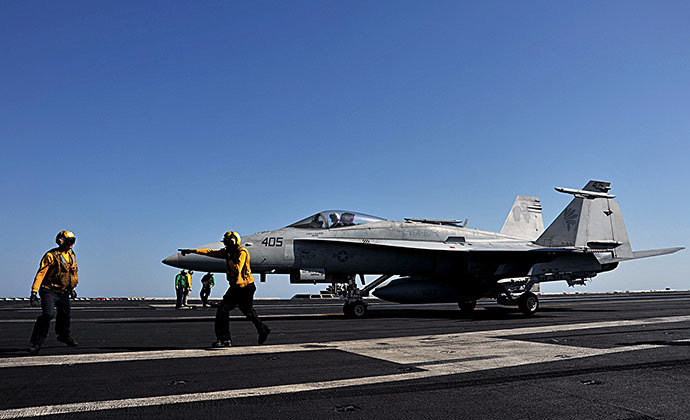 In this image released by the US Navy, sailors direct an F/A-18C Hornet on the flight deck of the aircraft carrier USS George H.W. Bush during flight operations in the Arabian Gulf on June 17, 2014. (AFP Photo / Maggie Keith)