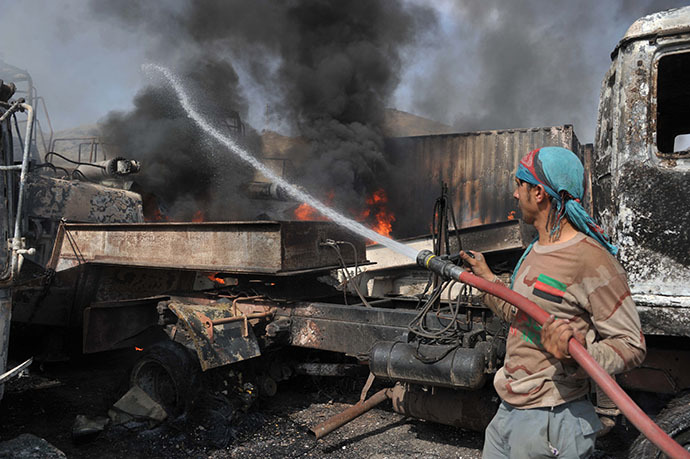 Afghan firefighters extinguish burning NATO military vehicles at the scene of a suicide attack at the Afghan-Pakistan border crossing in Torkham, Nangarhar province on June 19, 2014. (Reuters / Noorullah Shirzada)