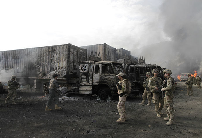 NATO troops walk near burning NATO supply trucks after, what police officials say, was an attack by militants in the Torkham area near the Pakistani-Afghan in Nangarhar Province June 19, 2014. (Reuters / Parwiz Parwiz)