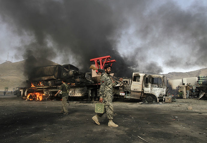 Afghan security forces walk near burning NATO supply trucks after, what police officials say, was an attack by militants in the Torkham area near the Pakistani-Afghan in Nangarhar Province June 19, 2014. (Reuters / Parwiz Parwiz)