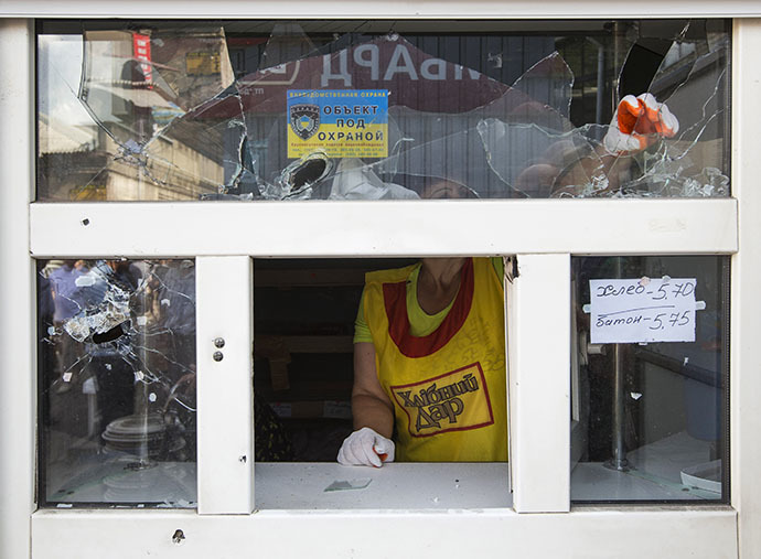 A bakery assistant removes broken glass from a window after overnight shelling on a market in the eastern Ukranian city of Slaviansk June 17, 2014. (Reuters / Shamil Zhumatov)