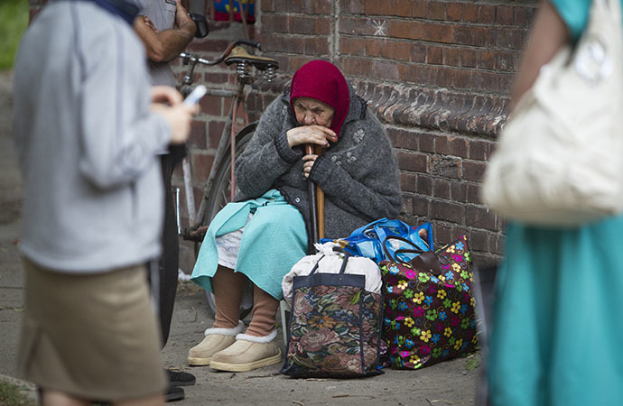 A woman sits on the ground while waiting for a bus to leave the eastern Ukranian city of Slaviansk June 17, 2014. (Reuters / Shamil Zhumatov)