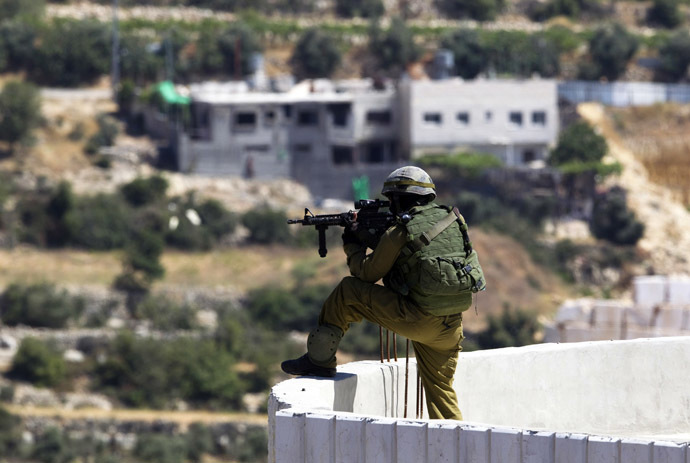 An Israeli soldier takes position during an operation to locate three missing teenagers, in the West Bank city of Hebron June 18, 2014. (Reuters/Ronen Zvulun)
