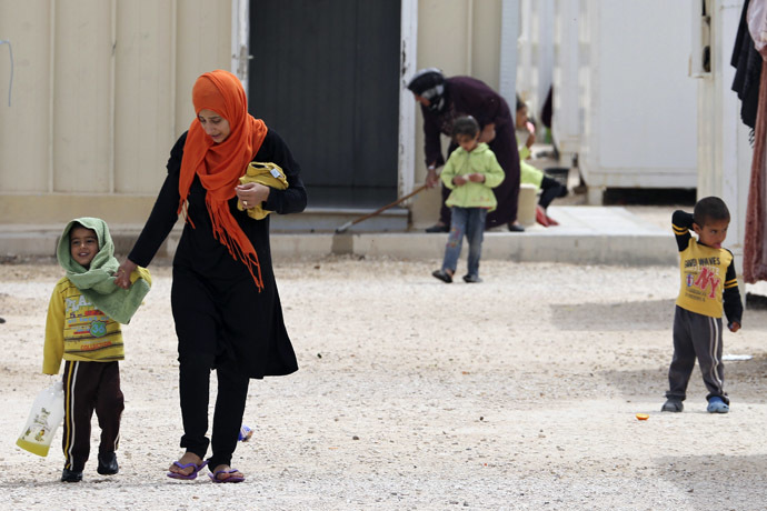 A Syrian refugee woman walks with her son inside the Mrajeeb Al Fhood refugee camp, east of the city of Zarqa April 13, 2014. (Reuters)