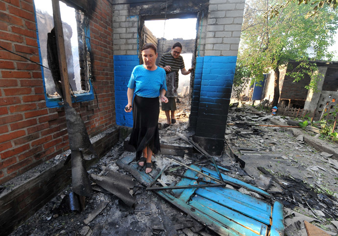 Local residents walk near a house destroyed during a night combat between Ukrainian and anti-government forces in the village of Semenovka, near the eastern Ukrainian city of Slavyansk, on May 23, 2014. (AFP Photo)