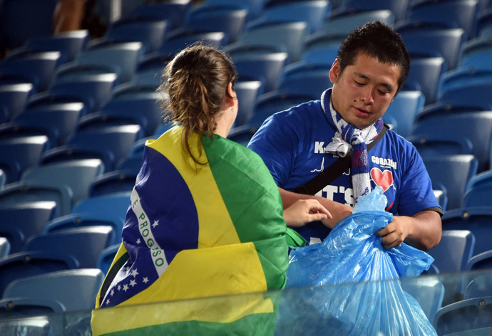 A Japanese fan cleans the tribune after a Group C football match between Japan and Greece at the Dunas Arena in Natal during the 2014 FIFA World Cup on June 19, 2014. (AFP Photo / Toshifumi Kitamura)
