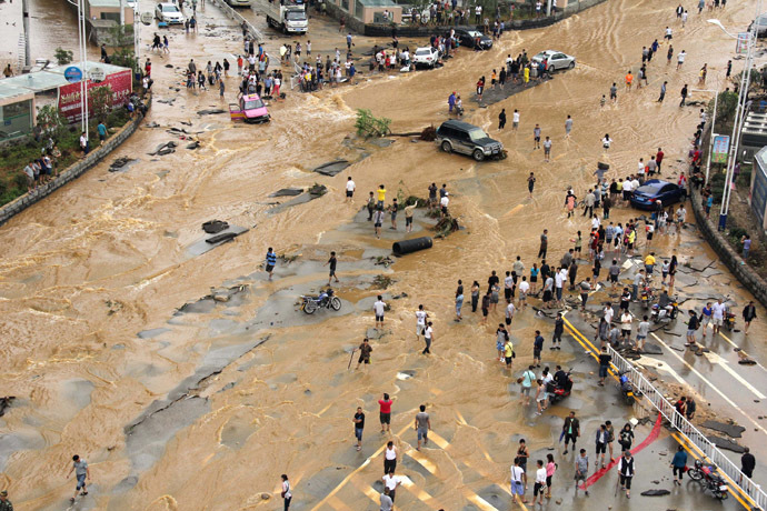 Residents make their way through a heavily-flooded street in Anshun city in Pingba county, southwest China's Guizhou province on June 3, 2014. (AFP Photo)