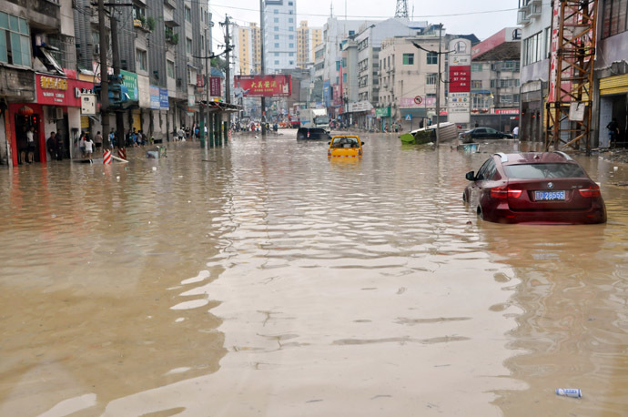 his picture taken on June 4, 2014 shows cars parked on a heavily flooded street in Shiqian county of Tongren, southwest China's Guizhou province. (AFP Photo)
