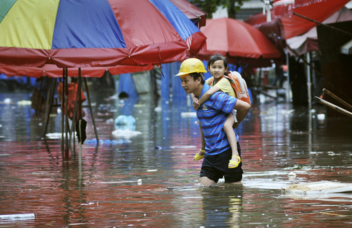 A man carries a girl on his back as he wades through a flooded street after heavy rainfalls hit Changsha, Hunan province June 20, 2014. (Reuters)