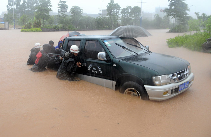 Rescue workers push a vehicle on a flooded street in Qinzhou, Guangxi Zhuang Autonomous Region, June 11, 2014. (Reuters)