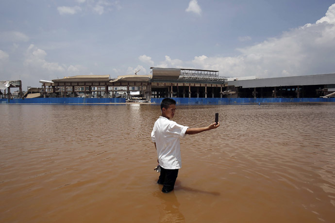 A resident takes a picture of himself standing in flood waters at a flooded area of Wujiaba airport in Kunming, Yunnan province June 9, 2014. (Reuters)