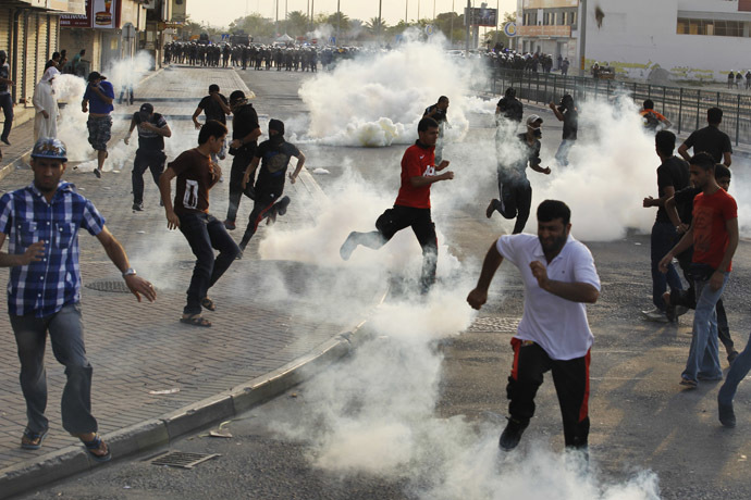 Anti-government protesters take cover from tear-gas fired by the police as they clash during a funeral procession for fellow protester Sayed Mohsen, in the village of Sitra south of Manama, May 27, 2014. (Reuters/Hamad I Mohammed)
