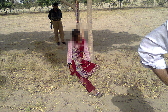A policeman stands near the body of Muzammil Bibi, 20, after policemen lowered her after she was found hanging from a tree in the town of Nawan Kot, located in Pakistan's Punjab province June 20, 2014. (Reuters / Irshad Hussain)
