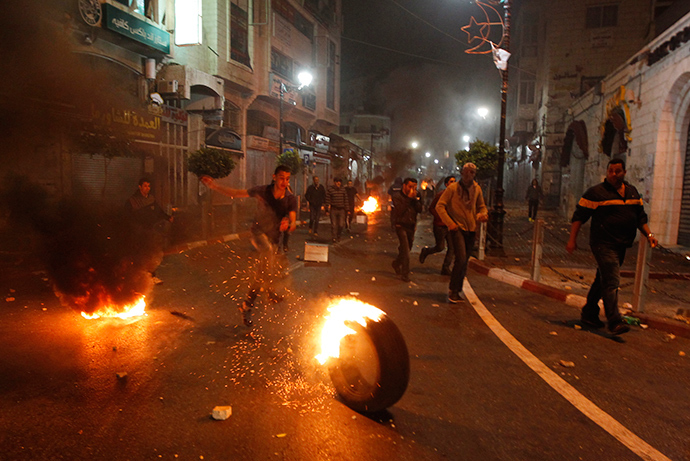 Palestinians set fire on tires during clashes with Israeli security forces taking part in the search for three missing teenagers early on June 22, 2014 in the West Bank city of Ramallah (AFP Photo / Abbas Momani)