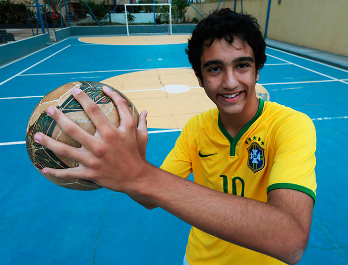 Joao de Assis, a member of the da Silva family with six relatives who all have six fingers on their hands, poses for a photo with a soccer ball at their home in Brasilia, June 20, 2014 (Reuters / Joedson Alves)