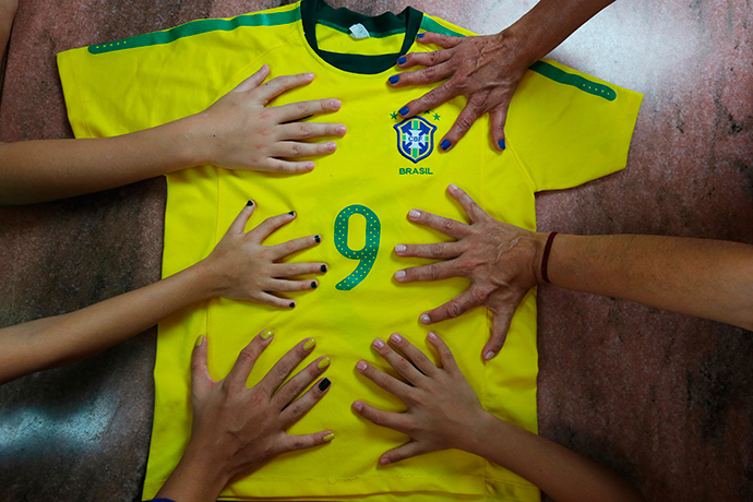 Members of the da Silva family pose for a photo with a national soccer jersey showing their hands all have six fingers, in Brasilia, June 20, 2014 (Reuters / Joedson Alves)