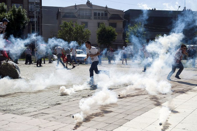 Kosovo Albanians run away from tear gas grenades fired by anti-riot police during clashes on June 22, 2014 in the divided town of Mitrovica. (AFP Photo / Armend Nimani)