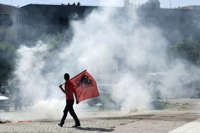 A Kosovo Albanian man, holding an Albanian flag, walks near tear gas fired by riot-police during clashes on June 22, 2014 in the divided town of Mitrovica. (AFP Photo / Armend Nimani)