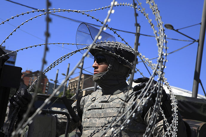 A U.S. soldier, part of a NATO peace force, places barbed wire on his Humvee during a protest in the ethnically divided town of Mitrovica June 22, 2014. (Reuters / Hazir Reka)