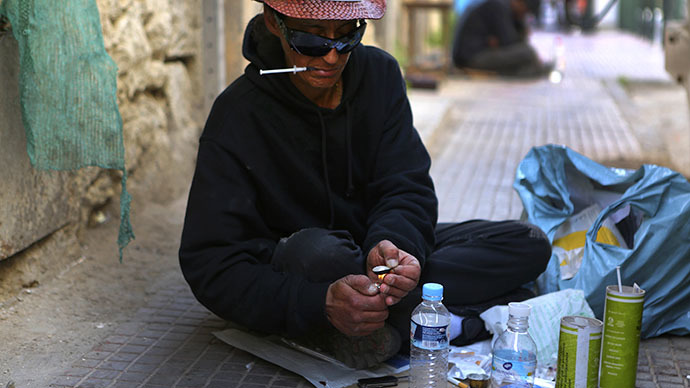 Vicky, a 40-year-old, Canadian-born, Greek drug addict, prepares a cocktail known as speedball, a cocaine and heroin mix, on a central Athens sidestreet (Reuters / Yannis Behrakis)