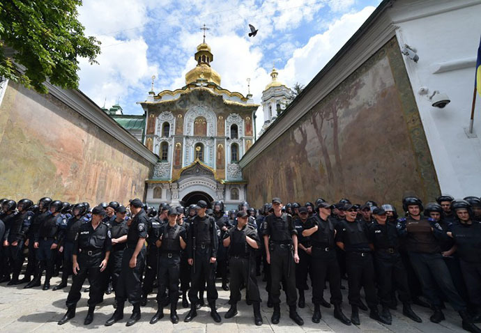 Ukrainian policemen guard the entrance of Kiev Pechersk Lavra, an Orthodox Christian complex of monasteries and cathedrals in Kiev, to prevent storming by activists of various pro-Ukrainian radical youth groups on June 22, 2014. (AFP Photo / Sergei Supinsky)