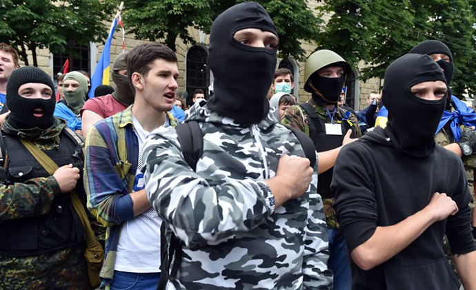 Activists of various pro-Ukrainian radical youth groups sing the anthem as policemen guardthe entrance of the Kiev Pechersk Lavra, an Orthodox Christian complex of monasteries and cathedrals in Kiev, to prevent storming by activists of various pro-Ukrainian radical youth groups on June 22, 2014. (AFP Photo / Sergei Supinsky)