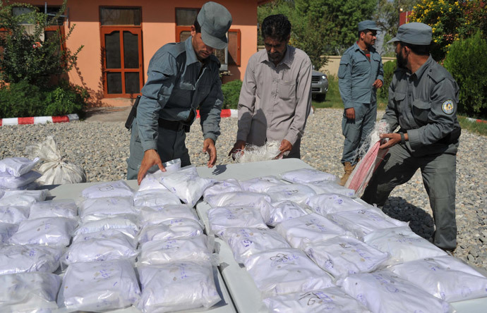 Afghan policemen count bags containing heroin as they are presented to the media at a police station in Jalalabad (AFP Photo / Noorullah Shirzada)