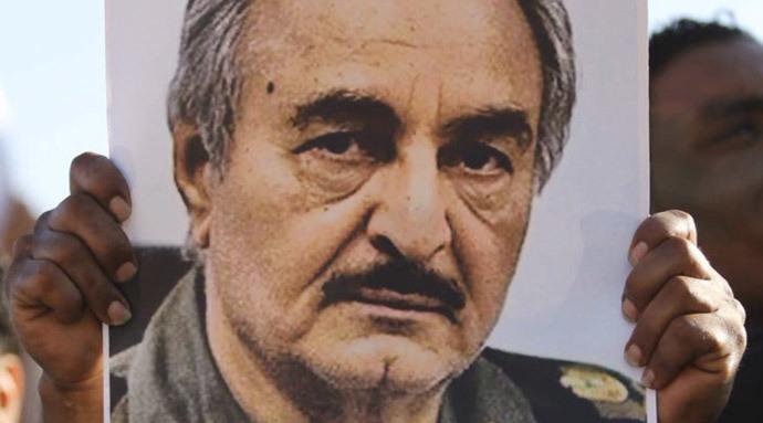 A man holding a poster of Khalifa Haftar (RT video screenshot)