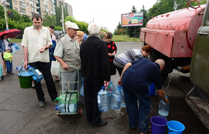 Residents queue up for water in front of a water truck in Kramatorsk, some 25 km south of Slavyansk on June 25, 2014. (AFP Photo / John Macdougall)