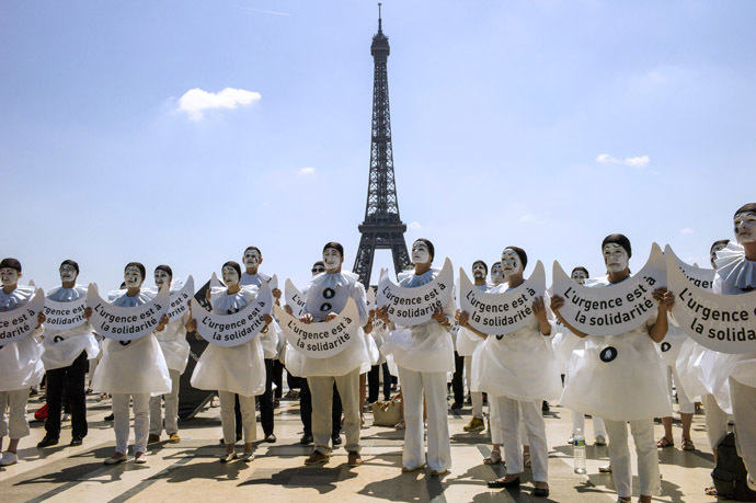 "People dressed as the traditionnal theatre character ""Pierrot"" hold placards reading ""Urgency is to solidarity"" as they take part in a demonstration against euthanasia for elderly and dependent people on June 24, 2014 on the Trocadero esplanade, also called the Parvis of Human Rights, near the Eiffel Tower in Paris. (AFP Photo/Fred Dufour)"