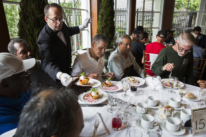 A waiter serves dessert to a table of men listening to Chinese millionaire Chen Guangbiao during a lunch he sponsored for hundreds of needy New Yorkers at Loeb Boathouse in New York's Central Park June 25, 2014. (Reuters/Lucas Jackson)