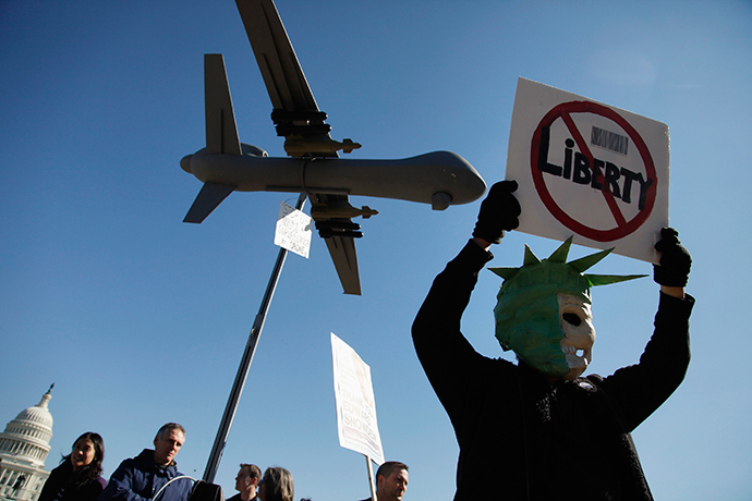 A protester wears a mask depicting a skull beneath the head of the Statue of Liberty, as he demonstrates beneath a model of a U.S. drone aircraft near the U.S. Capitol in Washington (Reuters / Jonathan Ernst)