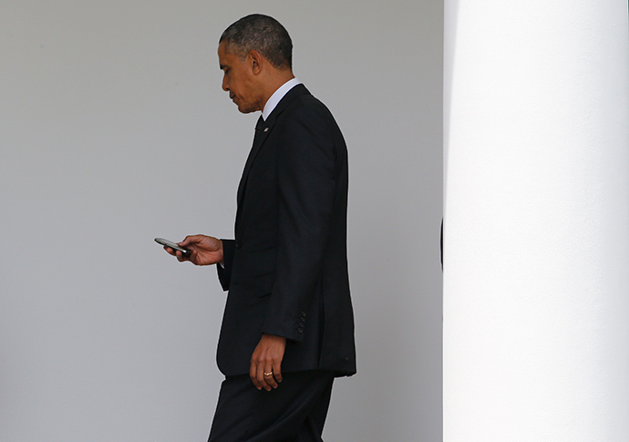 President Barack Obama checks his Blackberry smartphone (Reuters / Jim Bourg)