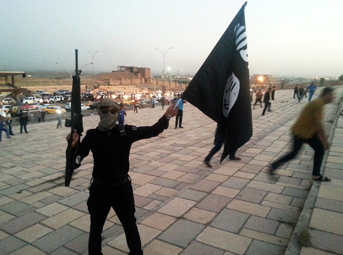 A fighter of the Islamic State of Iraq and the Levant (ISIL) holds an ISIL flag and a weapon on a street in the city of Mosul, June 23, 2014 (Reuters / Stringer)