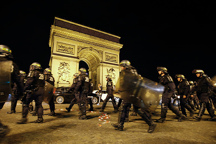 French CRS riot police officers secure the Arc de Triomphe as Algerian fans celebrate after Algeria's 2014 World Cup Group H soccer match against Russia, in Paris early June 27, 2014 (Reuters / Gonzalo Fuentes)