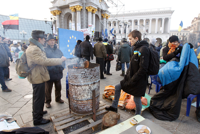 Pro-EU supporters huddle over a fire after spending the morning of November 28 at the protest camp in Independence Square in Kiev (Reuters / Vasily Fedosenko)