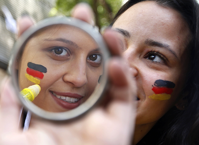 Stephanie, a fan supporting Germany's national soccer team, uses a stick to paint the German flag on her face before the broadcast of the 2014 World Cup Group G soccer match between the U.S. and Germany in Belo Horizonte June 26, 2014. (Reuters / Eric Gaillard)