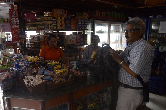 People shop at a minimarket during a power cut in Caracas, on June 27, 2014. (AFP Photo / Leo Ramirez)