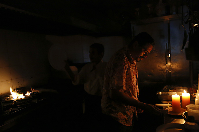 Restaurant workers try to finish up orders in the kitchen during a blackout in Caracas June 27, 2014. (Reuters / Carlos Garcia Rawlins)