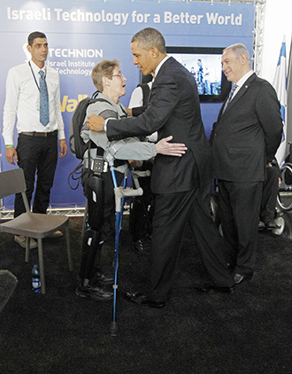 U.S. President Obama hugs U.S. Army Sergeant Hannigan as she wears an electronic leg technology named ReWalk during a tour of the technology expo in Jerusalem. (Reuters / Jason Reed)