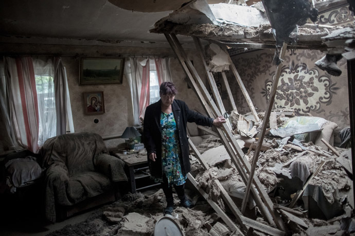 A resident of the settlement of Golubovka in Lugansk region is in her house following artillery shelling. (RIA Novosti/Andrey Stenin)