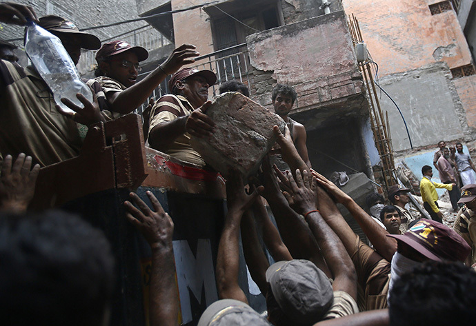 Rescue workers and volunteers load debris onto a truck at the site of a collapsed building in New Delhi June 28, 2014. (Reuters / Anindito Mukherjee)