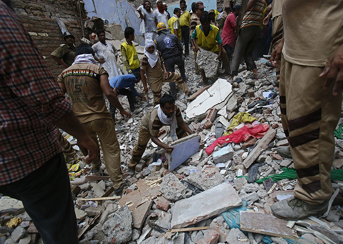 Rescue workers clear the debris from the site of a collapsed building in New Delhi June 28, 2014. (Reuters / Anindito Mukherjee)