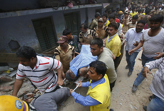 An injured man is taken to an ambulance from the site of a collapsed building in New Delhi June 28, 2014. (Reuters / Anindito Mukherjee)